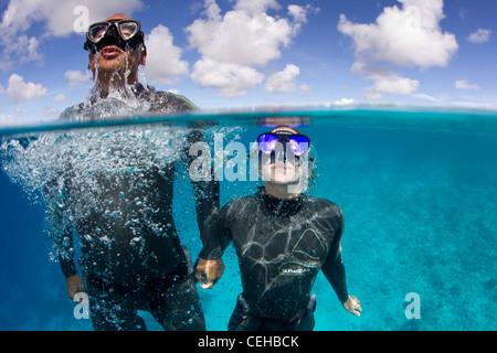 Freedivers ascending towards surface - Stock Photo