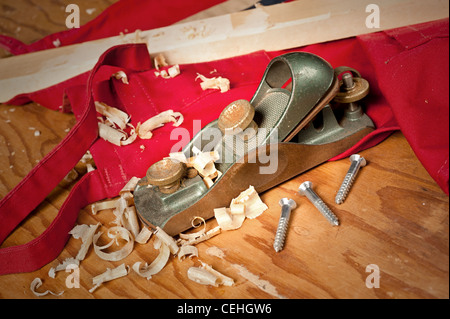 An old wood planer with curled shavings on a red workshop apron for use as a woodcraft inference. - Stock Photo