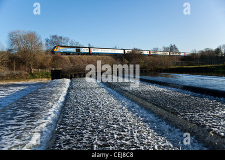 East Midlands Trains High speed train passing Pillings Lock weir on the River Soar, Barrow upon Soar, Leicestershire. - Stock Photo