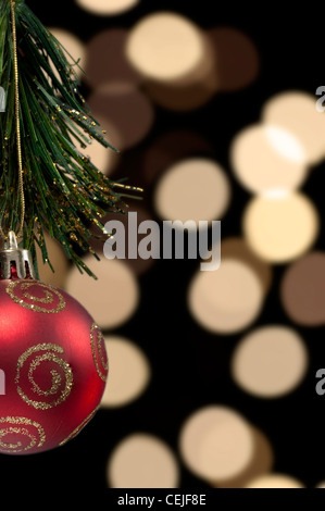 A red Christmas tree ball decoration against a background of out of focus blurred Christmas tree lights - Stock Photo
