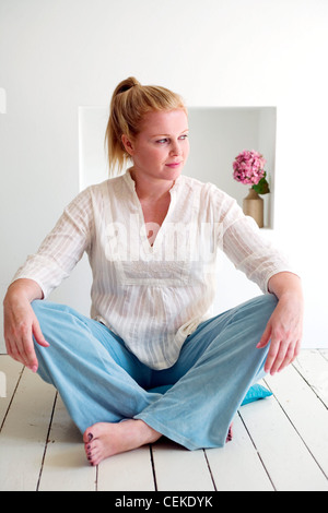 Larger female blonde hair off face in ponytail wearing cream collarless shirt and blue trousers sitting cross legged - Stock Photo