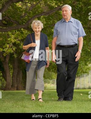 a senior couple walk through a park; edmonton, alberta, canada - Stock Photo
