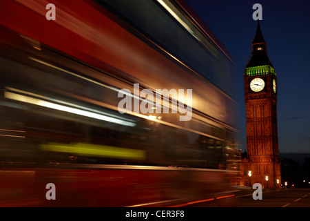 A red double decker bus passing Big Ben at night in Westminster. - Stock Photo