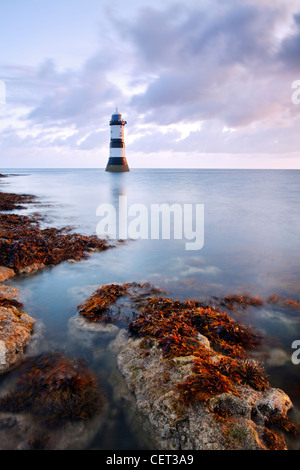 A view of Penmon Lighthouse at dawn on the coast of Anglesey in North Wales. - Stock Photo