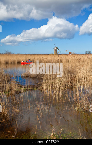 Canoeist on the River Thurne with the derelict Heigham Holmes Mill at Eelfleet Dyke in the distance on the Norfolk - Stock Photo