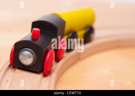 Toy wooden train on curving track. - Stock Photo