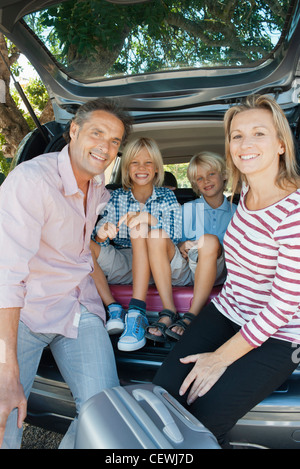 Family sitting together in back of car with open hatchback - Stock Photo