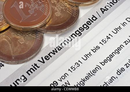 Verwarnungsgeld, daneben liegen einige Euro Münzen | fine for speeding, some Euro coins alongside - Stock Photo