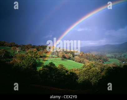 Storm light with rainbow against dark skies over Welsh hills. - Stock Photo