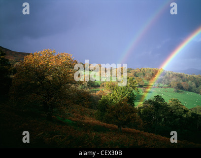 Storm light with double rainbow against dark skies over Welsh hills. - Stock Photo