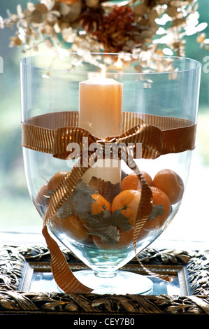 Decorating Gold at Christmas Large glass vase filled oranges, gold leaves and lit candle Wide gold ribbon tied in - Stock Photo