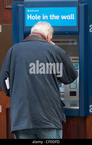 People using local cash Barclays 'Hole in the Wall' cash machine, England, UK. - Stock Photo