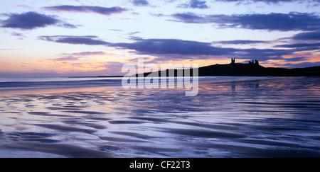 Dunstanburgh Castle at sunrise, Northumberland, England, UK. Viewed from Embleton Bay. - Stock Photo