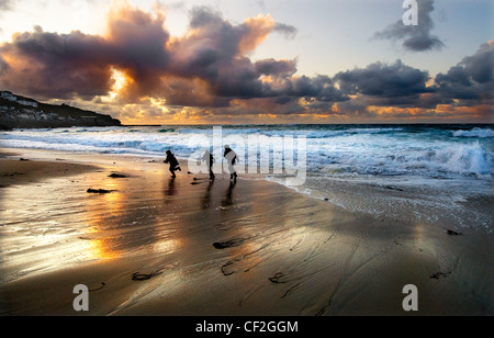 Three children play on the beach under a dramatic sky at Sennen Cove. - Stock Photo
