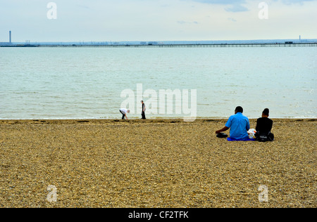 A couple enjoying a picnic on Jubliee Beach at Southend-on-Sea. Southend Pier, the longest pleasure pier in the - Stock Photo