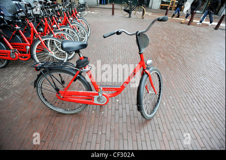 A typical red rental bicycle outside a shop in Amsterdam, Netherlands. - Stock Photo