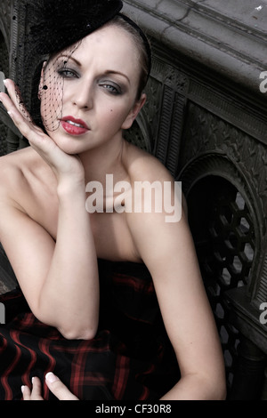 Female fair hair off her face, wearing a pill box hat black netting and strapless dress, smoky eyes make up and - Stock Photo