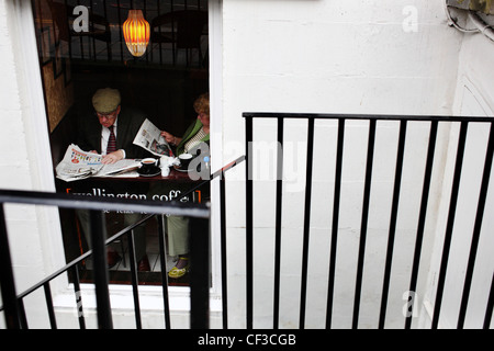 A couple reading newspapers in a cafe on Hanover Street. - Stock Photo