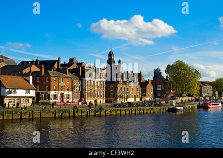 People sitting at tables outside bars and restaurants along the waterfront at King's Staith by the River Ouse. - Stock Photo