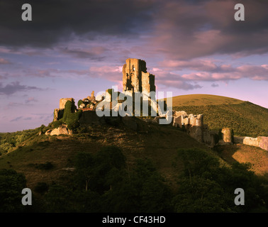 Late evening light on the ruins of the 11th century Corfe Castle in the Purbeck Hills. - Stock Photo