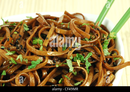 Bowl of stir fried udon noodles garnished with black sesame seeds and fresh mint with green chopsticks - Stock Photo