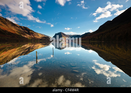 The surrounding mountainside reflected in the calm waters of Buttermere lake. - Stock Photo
