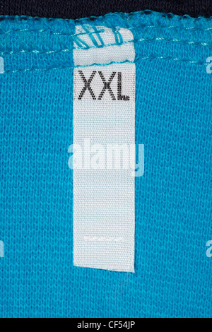 Label size XXL on blue cloth. Large size clothing. - Stock Photo