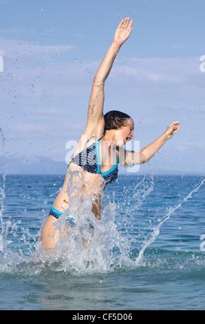 Greece, Ionian Islands, Ithaca, Woman swimming in sea - Stock Photo