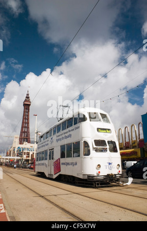 Tram running along a seafront on a sunny summer day at Blackpool. The town is believed to get its name from a drainage - Stock Photo
