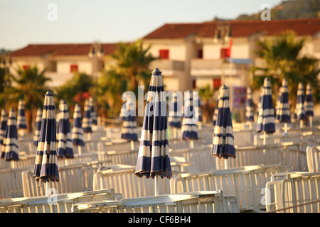 Deck-chairs and beach umbrellas neatly built rows on  beach in  morning next to cottages, shallow depth of focus - Stock Photo