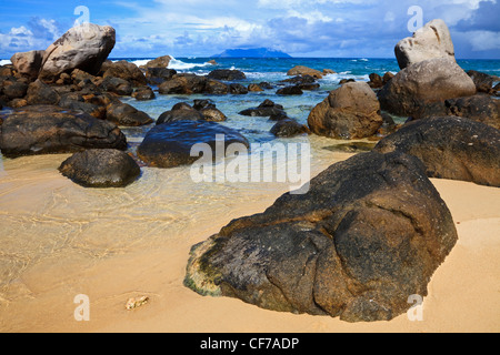 Near Sunset Beach, Mahe, Seychelles showing the granite rock formations and Silhouette Island on the horizon. - Stock Photo