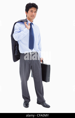Portrait of a businessman holding a briefcase and his jacket on his shoulder - Stock Photo