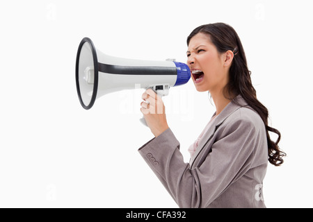 Side view of angry businesswoman shouting through megaphone - Stock Photo