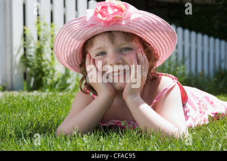 5 year old girl with sundress and hat laying on front lawn, canada. - Stock Photo