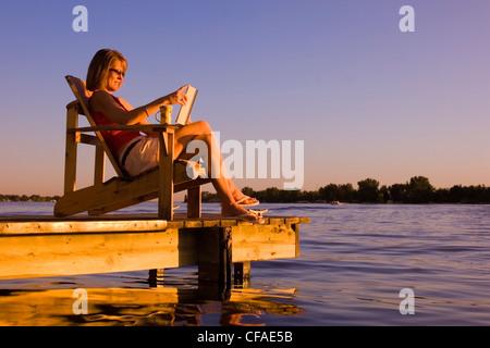 woman relaxing on dock at lake. Alberta, Canada. - Stock Photo