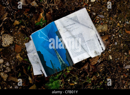 A book open on the chapter 'Man & Nature' left as rubbish on London roadside. - Stock Photo