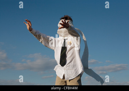 A boy in a private school uniform with a tie, with his eyes blindfolded by a toilet paper roll feels way with hands - Stock Photo