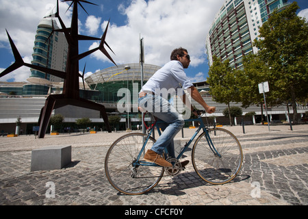 A cyclist rides through Parque das Nacoes, Lisbon, Portugal. - Stock Photo