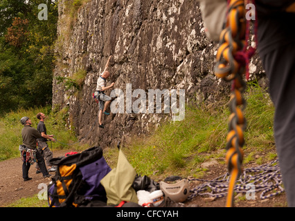 A climber sets out on a sport route at Benny Beg, Scotland while a belayer and equipment is out of focus in the - Stock Photo