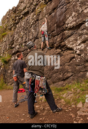 Two men, one belayer watch a climber stretch up patch of a sport route with a rope at Benny Beg, Scotland - Stock Photo