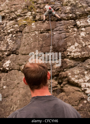 The back of the head of a belayer watches a climber travel up a wet patch of a sport route with a rope at Benny - Stock Photo