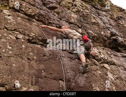 A climber goes for the clip on a lead sport route on quartz dolomite rock at Benny Beg Scotland. - Stock Photo