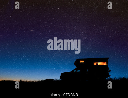 Camper under starry sky near Merritt, British Columbia, Canada. Cassiopea and the Andromeda galaxy are visible. - Stock Photo
