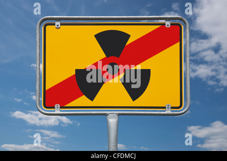 View of a end of the town sign with the symbol for radioactivity, background sky. - Stock Photo