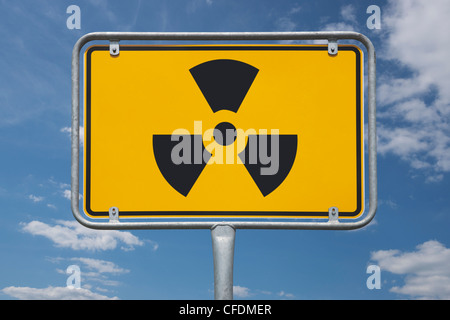 View of the entrance town sign with the symbol for radioactivity, background sky. - Stock Photo