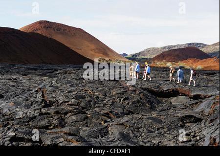 Tourists walking on lava flow on Isla Santiago, Sullivan Bay, Galapagos Islands, UNESCO World Heritage Site, Ecuador - Stock Photo