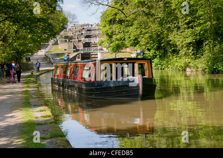 Narrowboat travelling on scenic rural waterway (Five Rise Locks, Leeds Liverpool Canal) with man & woman aboard - Stock Photo