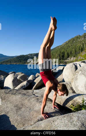 A young woman performs a handstand while doing yoga on granite boulders on the east shore of Lake Tahoe in the summer, - Stock Photo