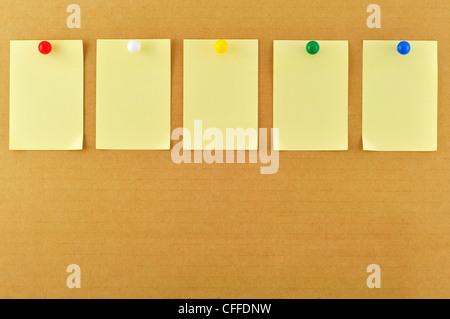 Blank sticky notes pinned on cardboard - Stock Photo