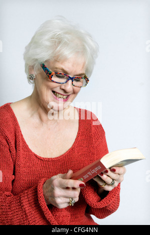Attractive senior lady in bright clothing reading book taken against a white background - Stock Photo